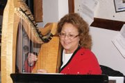 Charleah Firestone plays the harp Thursday night at the Festival of Trees at the Moffat County Courthouse.