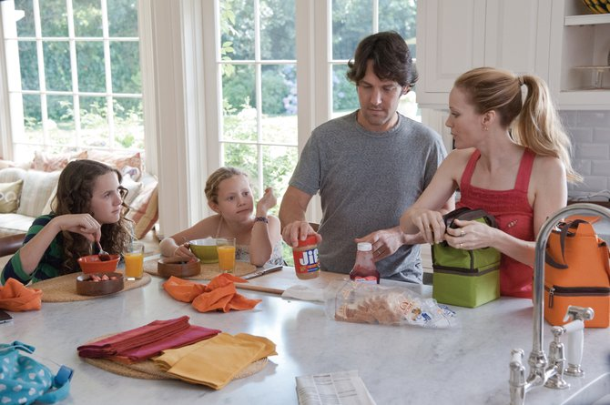 Parents Pete and Debbie (Paul Rudd, Leslie Mann) prepare their daughters (Maude and Iris Apatow) for another day in This Is 40. The movie is about a couple who vow to make some major life changes as they each turn 40.