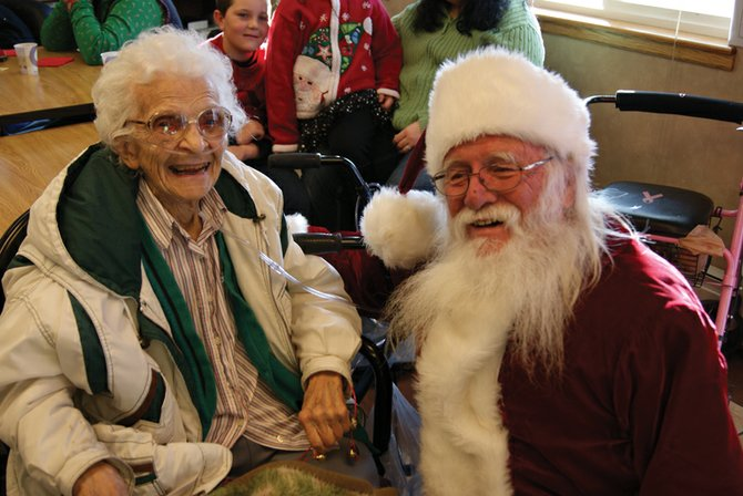 Elna Yoast, left, and Santa take a break from Sandrock Ridge Rehab and Care's festivities to pose for a picture.