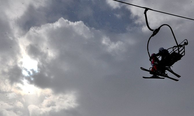 The sun breaks through clouds Sunday as a pair of skiers ride a lift up Mount Werner from the base area. A winter storm is expected to bring more snow to the area Monday and further guarantee a white Christmas.