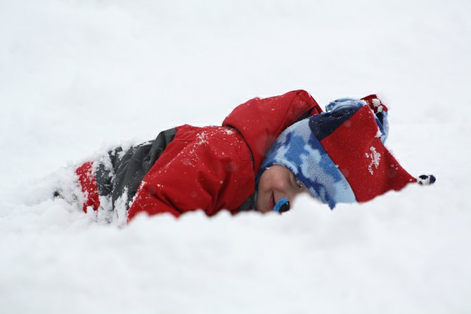 Brady Kub, two and a half, lays in the snow on Taylor Street after helping shovel the driveway.