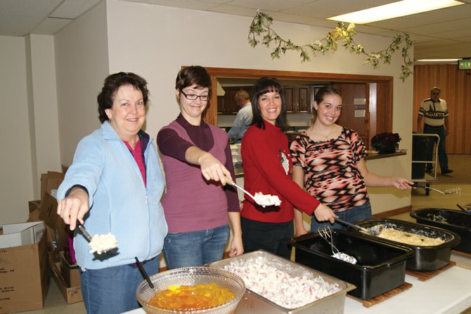 Chris Jarvis, from left, Sarah Bolton, Teri Bolton and Karen Bolton serve lunch at St. Michael's Catholic Church on Christmas Day. The three generations of family laughed, joked and brightening the day for those who came for lunch.