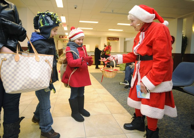 Donna Hellyer passes out candy to Isabella and Arnold Bomnin on Tuesday at Yampa Valley Regional Airport.  Hellyer has been greeting arriving passengers at the airport during the winter for 16 years.