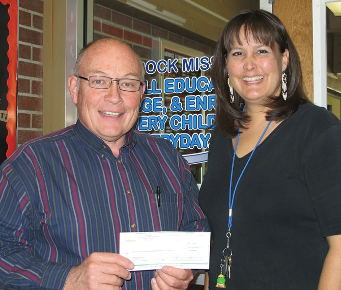 Chris Nichols, left, owner of the McDonald's in Craig, hands a check to Kamisha Siminoe, right, principal of Sandrock Elementary School for the funds raised during the McDonald's Teacher Night Challenge.