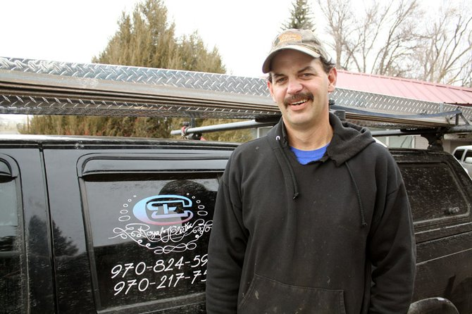 Greg Bauer, of Royal T Electric, stands in front of his truck outside of the Colorado Inn and Suites, where he does electrical work.