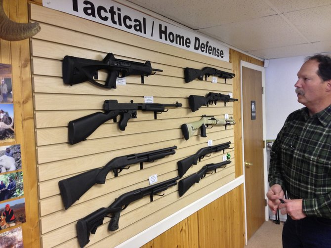 Elk River Guns owner Ken Constantine on Thursday discusses the guns he sells for tactical uses and home defense.