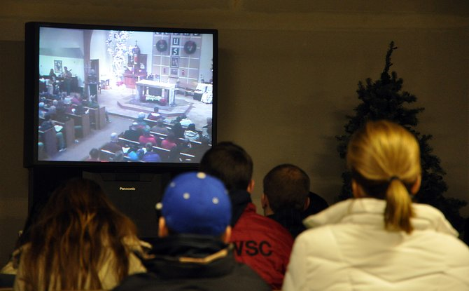 Holy Name Catholic Church parishioners watch Mass on a TV on Sunday in the basement of the church. An expansion project is under way to double the amount of worship space in the church.