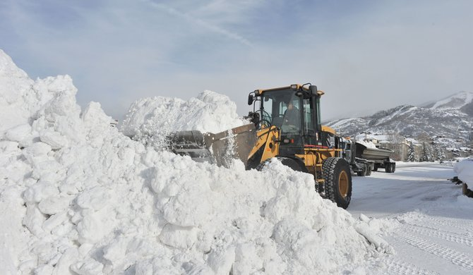 Mike Andrews uses a front-end loader to move snow out of the parking lot of a condominium complex to a dump truck waiting to move the snow to another location. Local snow removal companies have been busy the past several weeks after a series of winter storms made this the sixth snowiest December on record.