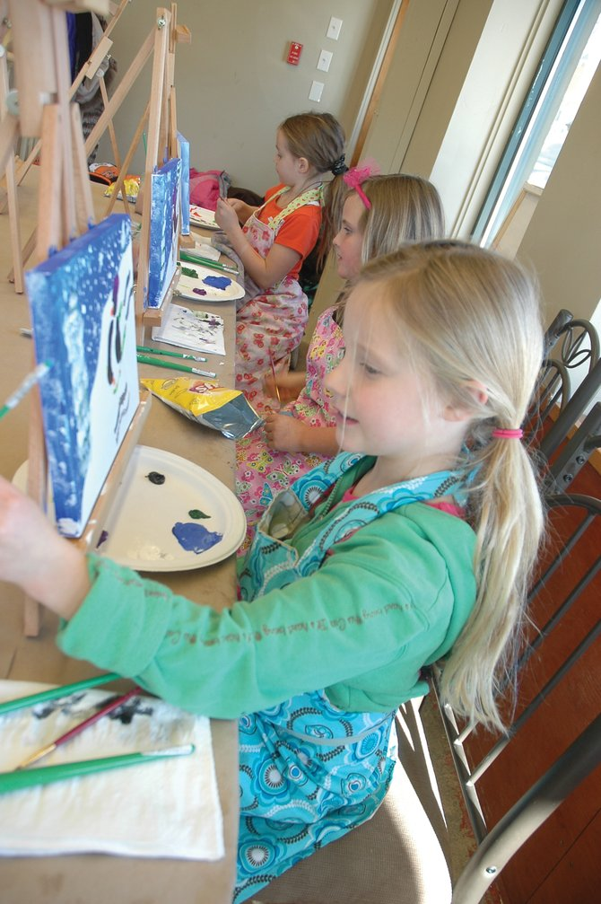 Kaelyn Radway, 7, works on her penguin painting Friday at Splatz Canvas and Wine. The new downtown business is open to special events, families, couples and groups of friends interested in a unique night on the town.