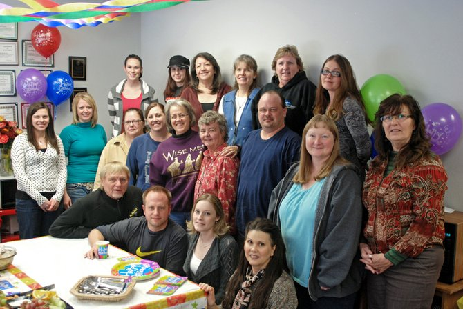 Marie Peer, center row in the purple sweater, poses with her friends, family and coworkers last month during a party in her honor. On Friday Peer will retire from the Moffat County Department of Social Services after 43 years and 11 months of service.