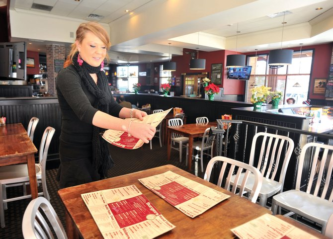 Waitress Karli Quarto sets up a table at Big House Burgers &amp; Bottlecap Bar  in Steamboat Springs. Local business owners continue to struggle with ways to keep costs down while providing employees with affordable health care.