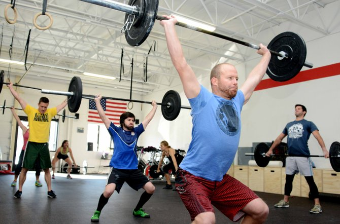 Nate Johansing lifts in front of a section of a CrossFit class at Fusion Fit in Steamboat Springs on Monday. The gym moved into a new location in Riverside Plaza earlier this month.