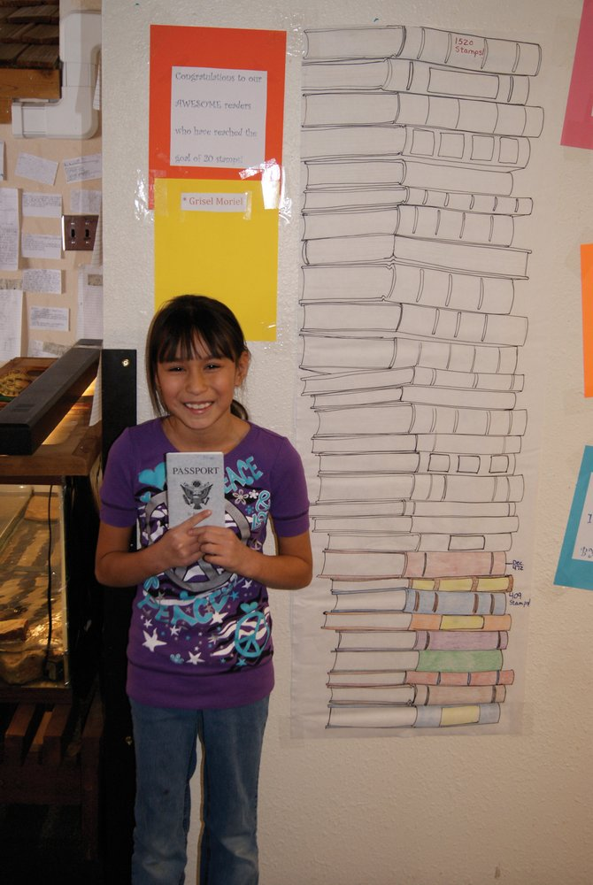 East fourth grader Grisel Moriel stand next to the chart tracking student progress in the Passport to Reading program. Moriel is the only student with her name on the list of those who have met the goal of reading 20 books.