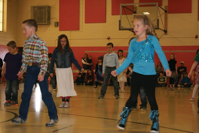 Sunset Elementary School second grader Kannadis Peroulis, left, and Aftyn Kawcak, right, dance during a performance Wednesday at the school. Music and physical education teachers teamed up to teach students the dances, culminating in performances for parents and family.