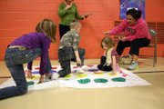 Serenity Stetler, 4, in stripes, participates in a literacy themed Twister game at the Literacy Carnival at Sunset Elementary School.