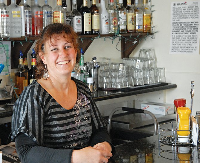 Ann Marie Roberts stands behind the bar at Double Barrel Steakhouse in Craig. Roberts is the Moffat County High School girls golf coach and has become more involved in the community since moving back to Craig to help operate the Double Barrel Steakhouse with her husband.
