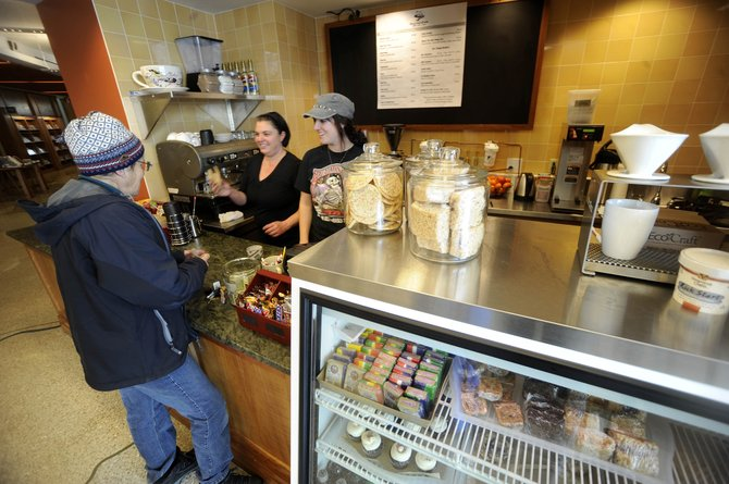 Barista Grace Martin, right, and MountainBrew co-owner Tasha Compos serve a snack to Steamboat Springs resident M.L. Mackie on Friday at the coffee shop's new location inside Bud Werner Memorial Library.