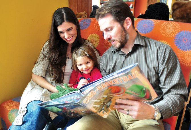Amy Minotto, her daughter Eva and husband, Jeff, read a book Tuesday afternoon at Bud Werner Memorial Library. Amy is in need of a marrow transplant and is hoping to raise awareness of the National Marrow Donor Program to help herself and others who need transplants.