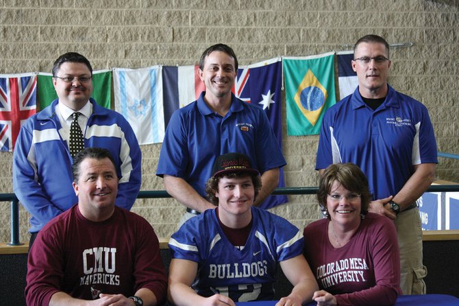 Michael Samuelson, a senior at Moffat County High School, will play football at Colorado Mesa University next year. He signed with the school Wednesday, along with his parents, Mark and Shannon (front) and (back row, from left) Moffat County School District Athletic Director Jeff Simon, head football coach Kip Hafey, and assistant coach Lance Scranton.