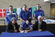 Jacob Teeter, a senior at Moffat County High School, signs his letter of intent to play football at the United States Merchant Marine Academy next year. Teeter was planning on attending a service academy, and was invited to join the USMMA football team recently. He was joined by his grandparents, Mary and Gene Teeter (front), as well as (back row, from left) Moffat County School District Athletic Director Jeff Simon, head football coach Kip Hafey and assistant coach Lance Scranton.