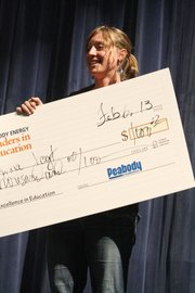 Brynna Vogt, a seventh grade science teacher at Craig Middle School, accepts a check Wednesday as part of the Peabody Leaders in Education award, which she was presented with during a surprise assembly.