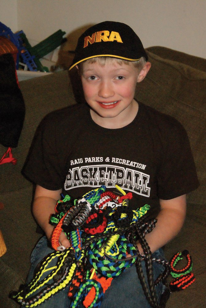 Logan Duke, 10, holds paracord bracelets, lanyards and keychains he's created for his business. Duke began three months ago and has already made impressive profits.