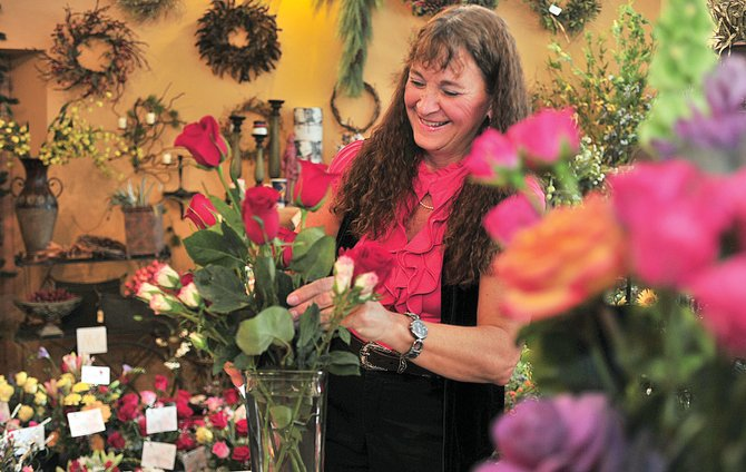 Cindy DeRenzo works to put together a bouquet for a customer at Steamboat Floral on Wednesday morning. The local flower shop was bustling Wednesday as workers rushed to get those Valentine orders put together and out the door.