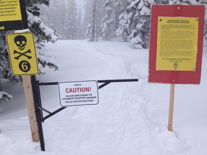 Skiers have to pass through a gate and several warning signs before going into the backcountry at Steamboat Ski Area.