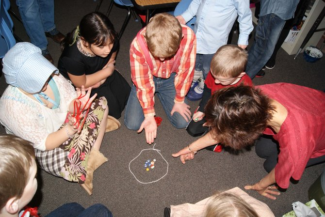 Sunset Elementary School third-grader Evan Allen, center, plays marbles during a party celebrating the class's graduation from Apple Valley School. Apple Valley School is a unit where students experience what it was like to go to school back in 1853.