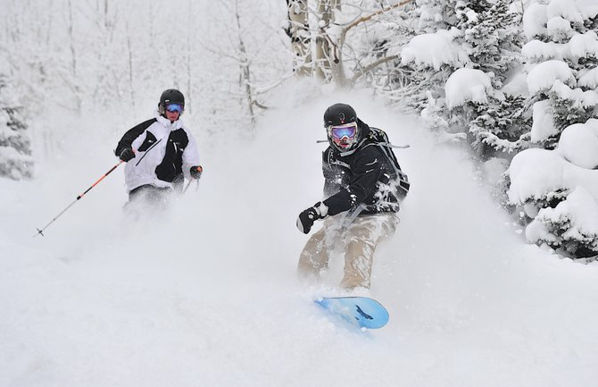 Snowboarder Dustin Eldridge and skier Jeremy Gray dive through the powder under the Sundown Express lift   Friday afternoon. The latest storm helped Steamboat Ski Area surpass last season's total snowfall.
