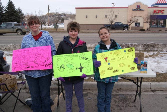 Vanessa Libbee, 13, Kyanna Woods, 12, and Kristi Barnes, 10, hold signs they made to help draw in customers to purchase girl scout cookies. The girls were at Walgreens from 11 a.m.-4 p.m. Sunday selling cookies.