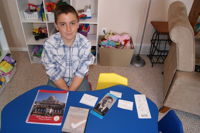 Tristan Farquharson, 12, sits in his home with items from his January trip to the presidential inauguration. Farquharson was one of about 1,500 middle school students from across the nation invited to attend the conference and inauguration.