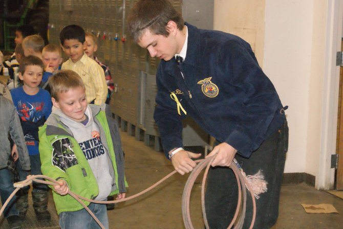 Moffat County High School senior and FFA president Bow Richardson shows Sandrock Elementary School kindergartner Trystin Gallegos how to properly hold the rope to prepare for roping. MCHS students in FFA hosted barnyard day for district kindergartners as part of national FFA week.
