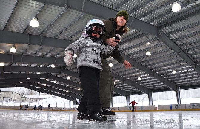 Paula Jaconetta teachers her daughter, Lupita, how to ice skate Sunday in Oak Creek. The town this year revived its Winterfest event and hosted a day of ice skating, tubing and sledding.
