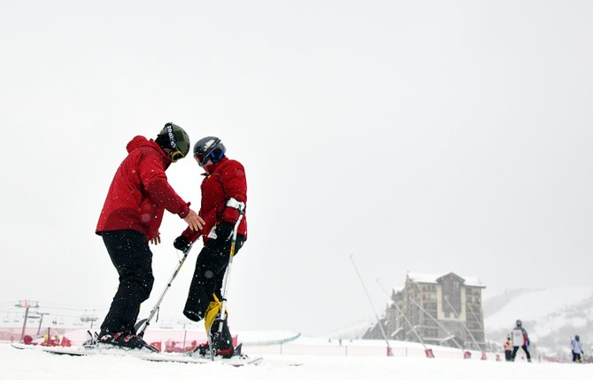 Chris Babcock, left, helps Montana Dalman learn to ski Tuesday at Steamboat Ski Area as part of the Sunshine Kids program. Montana lost her left leg in the treatment of a rare form of bone cancer. She quickly learned to ride on a set of adaptive skis.