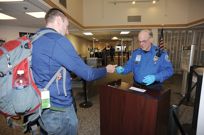 Passenger Mike Slavens hands his identification to TSA officer Rob Roberts at the Yampa Valley Regional Airport on Thursday afternoon.