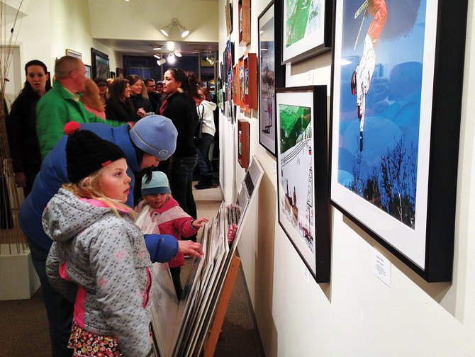 Madeleine Erps, 6, gazes at artwork on the wall of the Steamboat Springs Center for Visual Arts during First Friday Artwalk on Friday. The monthly downtown event has flourished in its five-year history. 