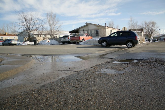 A car passes by a pothole on West Ninth Street in the Shadow Mountain subdivision.