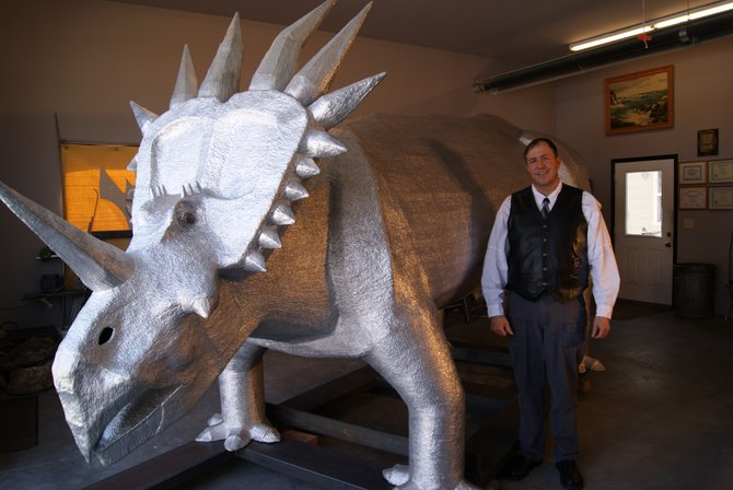 Rick Kawchack stands next to an aluminum sculpture of a Styracosaurus he spent two years creating. The sculpture weighs more than 2,000 pounds and contains more than 1.5 million spot welds.