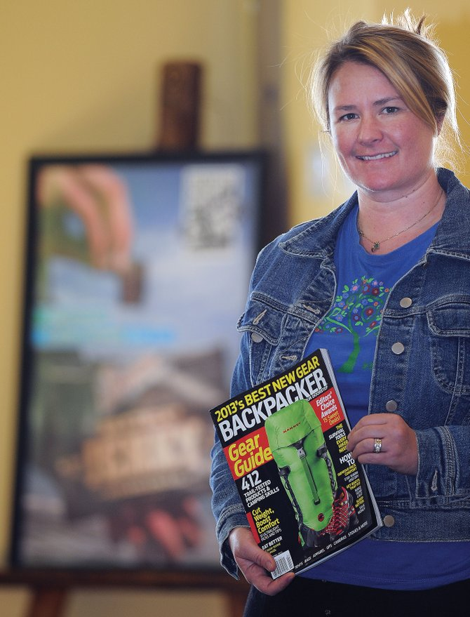 Sweetwood Cattle Co. General Manager Becca Fix holds the latest edition of Backpacker Magazine in front of the Editors' Choice Award presented by the editors of the magazine. Big Agnes also won an Editor's Choice Award for its Scout UL2 tent.