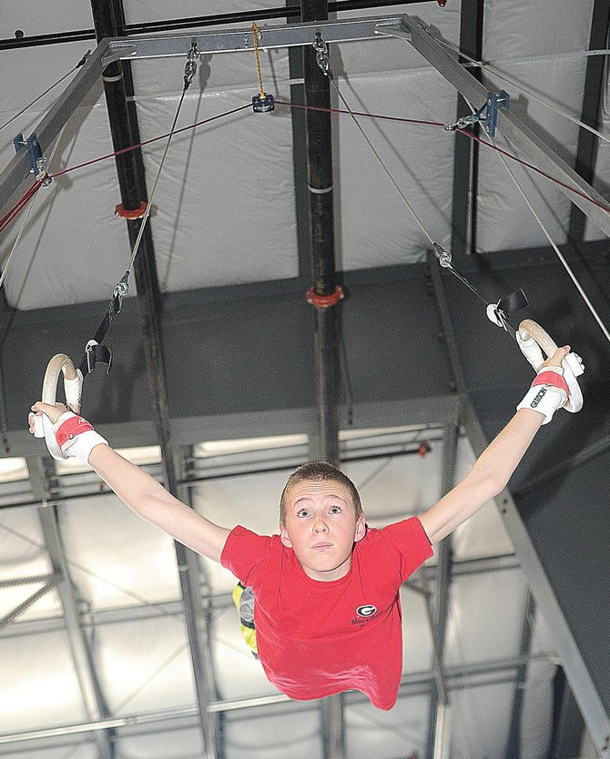 Steamboat Springs gymnast Eric Casey practices his routine on the rings Thursday afternoon at Excel Gymnastics. The local gymnastics center will host the Colorado Mens State Gymnastics Championship Meet this weekend. Competition begins Friday night and will continue all day Saturday and Sunday.
