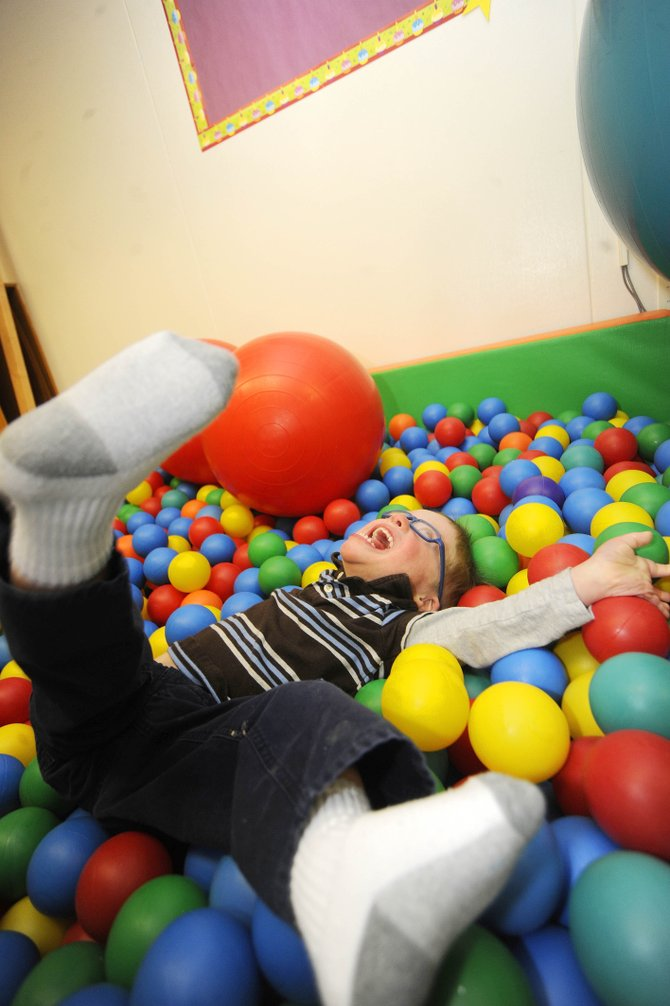Lewis Kleckler plays in a ball pit as part of his occupational therapy.