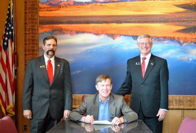 Senate District 8 Sen. Randy Baumgardner, R-Cowdrey, left, and House District 57 Rep. Bob Rankin, R-Carbondale, right, pose with Gov. John Hickenlooper during the signing into law of House Bill 13-1203. The measure, carried by Rankin and sponsored by Baumgardner, eliminates the requirement of political subdivisions of the state to submit certain reports on an annual basis.
