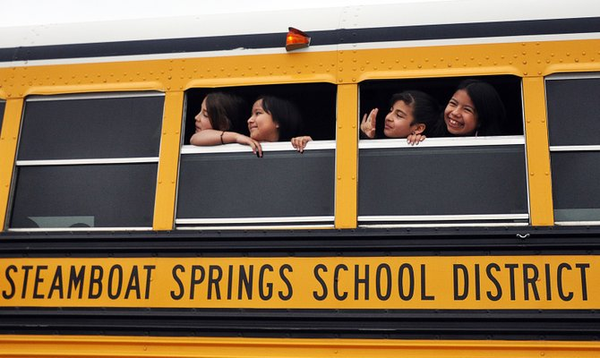 Strawberry Park Elementary School students, from left, Yoalli Loya, Veronica Chavez, Evelyn Tarango and Marina Chavez wave and gesture to classmates Wednesday from their school bus. Some last-minute amendments to a major school finance bill has improved the Steamboat Springs School District's financial outlook.