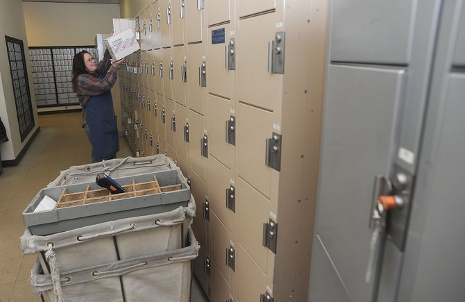 U.S. Postal Service employee Chris Blossom puts a package in a box at the Sundance at Fish Creek station  Monday afternoon. The Postal Service confirmed that it will consolidate the Sundance location into its downtown branch in an effort to save an estimated $1 million during 10 years.