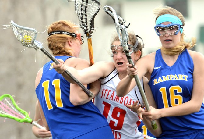 Steamboat's Nikki Fry tries to fight through a pair of Rampart defenders Friday. Fry scored five times in the game, matching sophomore Teagann Yeager for the team high. Yeager scored with two seconds remaining to force overtime, but the Sailors couldn't hang on, falling, 15-14.