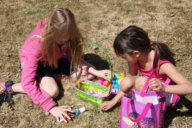 McKenzie Guevara, 10, and Nevaeh Lira, 8, look over their finds after the Easter egg hunt at Sandrock Ridge Care & Rehab on Sunday.