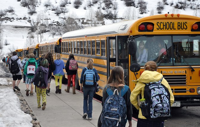 Students board a long line of buses last month at Steamboat Springs Middle School. The Steamboat School Board is considering asking voters here in the fall to approve a property tax increase to support local schools.