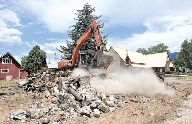 Dale Franks, of Duckels Construction, uses an excavator in July to remove what remains of an old house, which was owned by the Holy Name Catholic Church to make way for the church's planned expansion. The value of building permits issued in Routt County through the first three months of 2013 is up 33 percent over the same period in 2012.