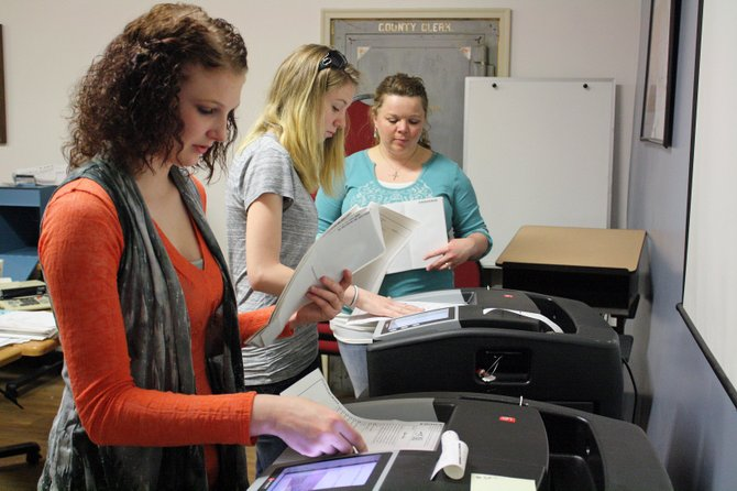 Alexa Criswell, left, Kaci Meek and Tori Pingley send ballots through counting machines at the Moffat County Courthouse for Tuesday's City Council and mayoral elections.